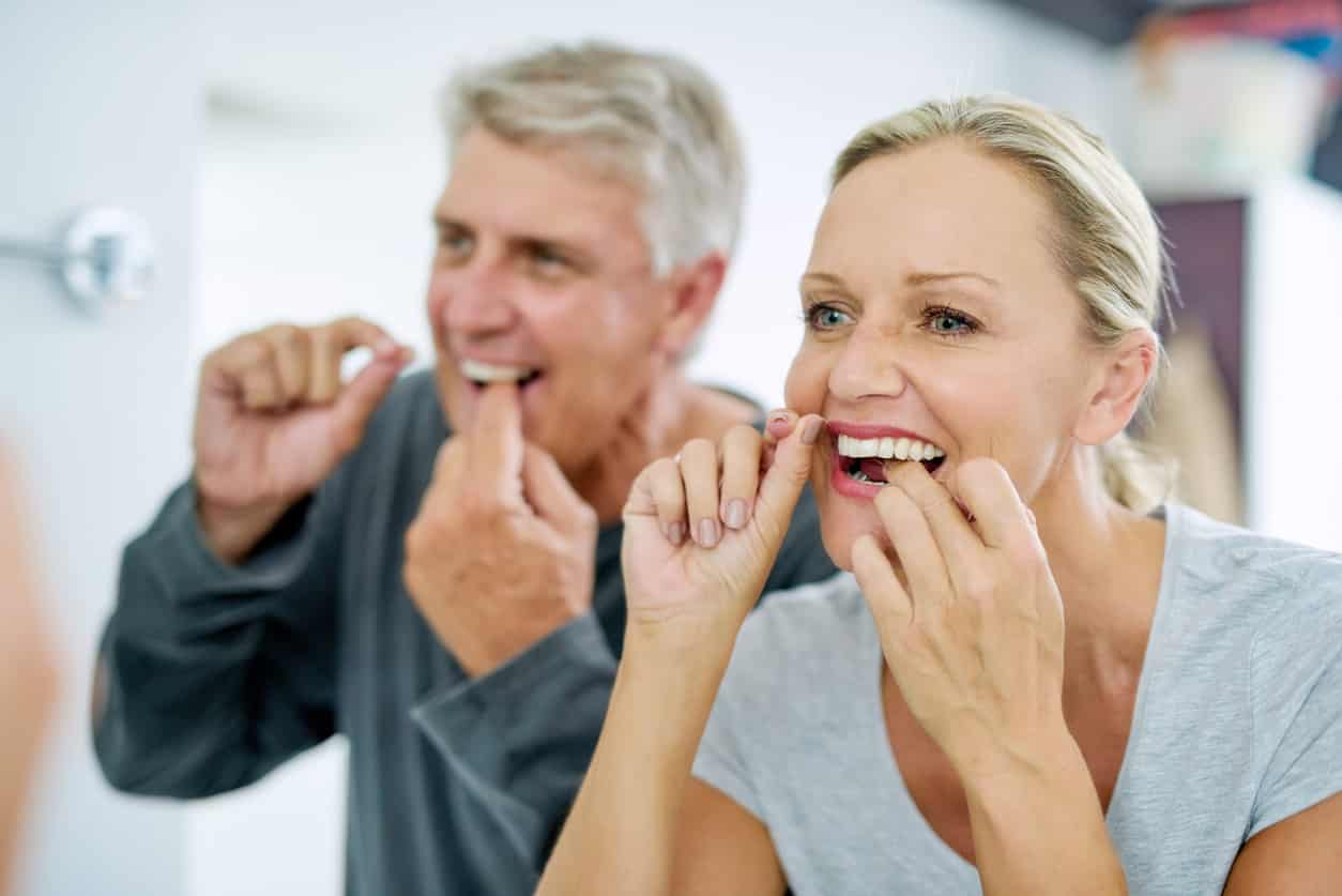 Cropped shot of a mature couple flossing their teeth in the bathroom