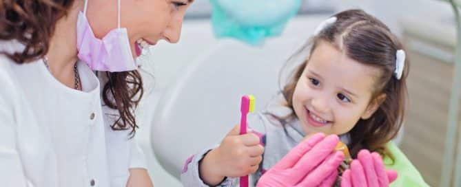 dentist helping a young girl to understand hygiene
