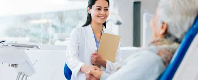 female dentist shaking hands with older woman in dentist chair