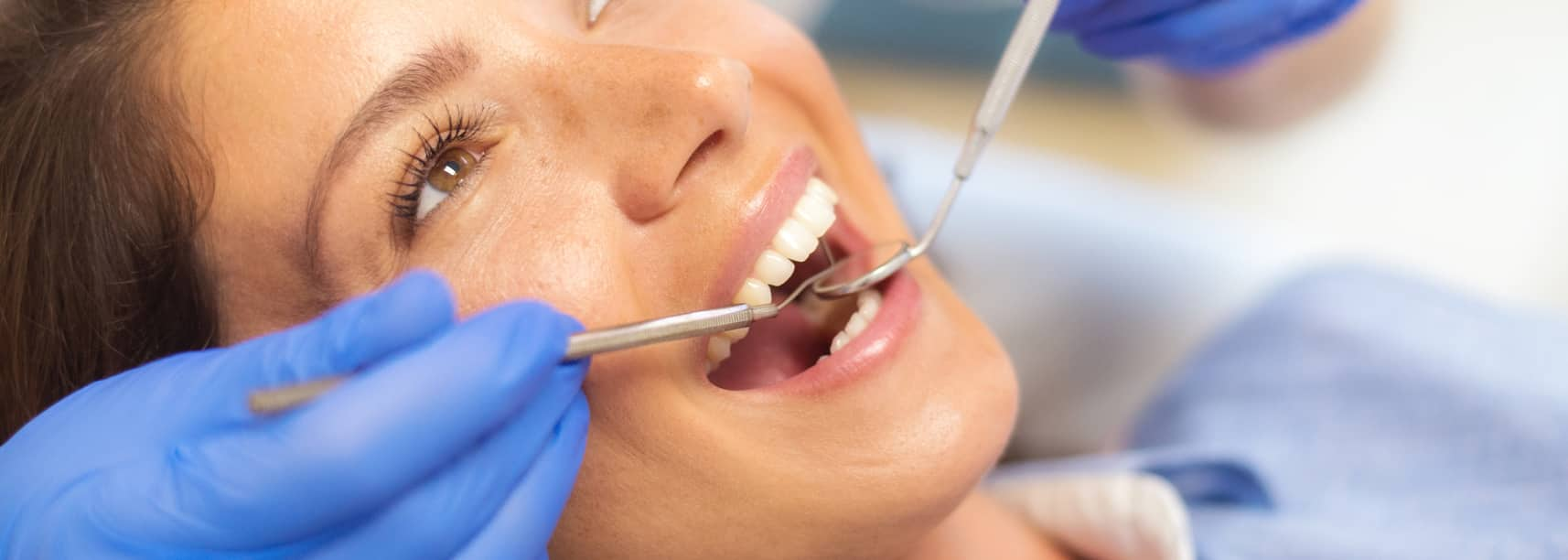 woman at the dentist getting teeth checked and fluoride treatment