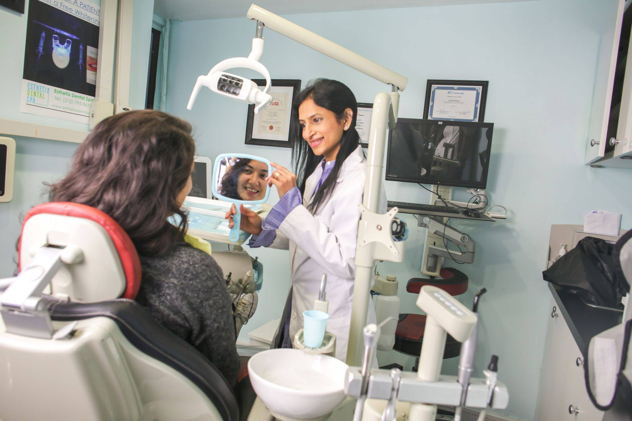 Dr. Divya Adusumilli with a happy patient seeing her new smile